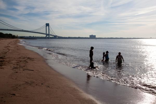 A family plays in the sea on South Beach, Staten Island, NY